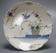 An 18th century faience dish, painted in polychrome enamels, 23cmCONDITION: Generally good with