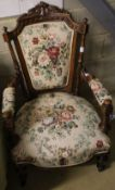 A late Victorian carved walnut upholstered open armchair