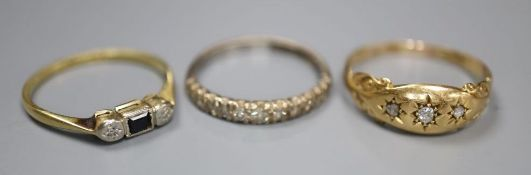 Three assorted 18ct and gem set rings including diamond half eternity, size N, and three stone