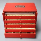 A Mah Jong set in red stained wood case