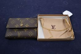 A Louis Vuitton purse, with pouch and box.