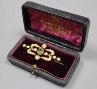 An Edwardian 15ct, split pearl and green garnet? set scroll bar brooch, 39mm, gross 4.7 grams.