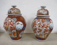 A near pair of Japanese porcelain lidded vases together with a blue and white vase and a