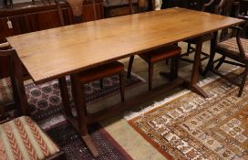A Gordon Russell walnut dining table, circa 1930, on chamfered double end supports and central