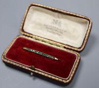 A yellow metal and graduated eighteen stone emerald set bar brooch, 36mm, gross 1.9 grams.