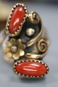 An Arts & Crafts yellow and white metal and two stone cabochon coral set triple shank dress ring,