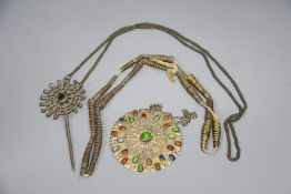 A South American poncho pin, a Turkoman paste and metal medallion and a West African tribal