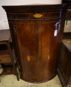 A George III inlaid mahogany bow-fronted hanging corner cupboard, having geometric line and shell