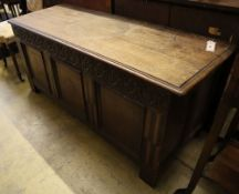 A 17th/18th century inlaid oak coffer with panelled front and planked top, width 145cm depth 53cm