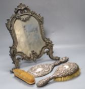 A Victorian cast metal easel mirror and a white metal mounted brush set