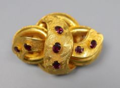 A Victorian yellow metal and seven stone garnet set scroll brooch, 47mm, gross 13.1 grams.CONDITION: