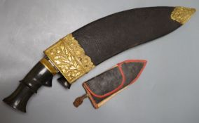 A kukri with skinning knives, leather sheath with elaborate embossed gilt metal mounts, blade 36cm