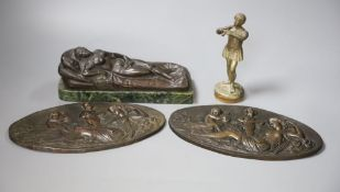 A bronze of a reclining female nude, a pair of plaques and a boy musician