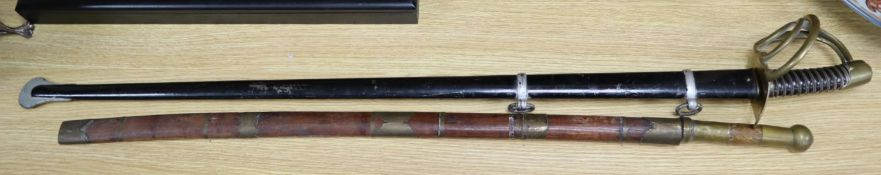 A French Cuirassier sword, blade 93cm, together with an Eastern brass mounted sword with wooden