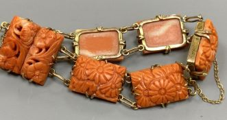 An early 20th century yellow metal seven stone coral panel set bracelet, carved with flowers, with