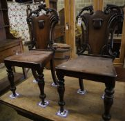 A pair of Victorian mahogany hall chairs (one a.f.)