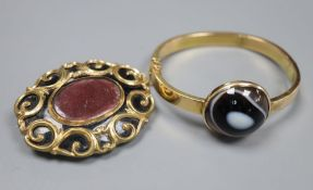 An early 20th century yellow metal (stamped 15) and banded agate set hinged bangle (repaired) and