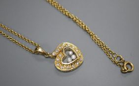 A modern Chopard style 18k and 'floating' diamond set heart shaped pendant, on a 750 chain,