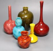 A collection of Burmantofts faience pottery vases, comprising a dark pink ground bottle-shaped