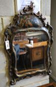 An 18th century style chinoiserie wall mirror, the cartouche shaped plated within cushioned