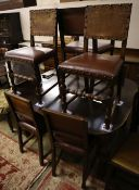 A 1930's oak extending dining table 234cm extended (two spare leaves) and seven dining chairs (one