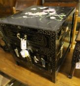 A Chinese black-lacquered brass-mounted small two-door cabinet, the door panels decorated with