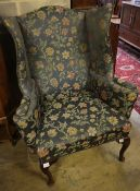 A George I style mahogany framed wing armchairCONDITION: Fading and wear to the upholstery,