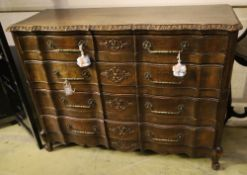 A 20th century French oak commode, fitted four long drawers with carved decoration, width 122cm,