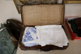A quantity of mixed table linens in a suitcase