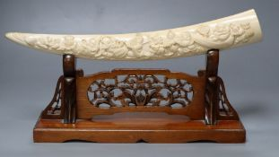 A Japanese ivory 'Seven immortals' tusk carving, early 20th century, wood stand, signed, 44cm