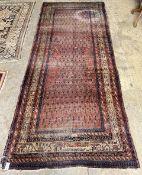 A Shirvan red ground carpet, 330 x 134cm