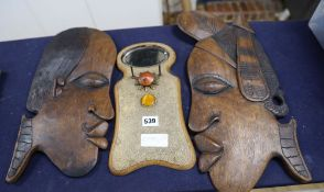 Two carved wooden face masks and a shagreen mirror