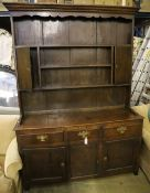 A mid-18th century oak dresser having later boarded plate rack over short drawers and panelled