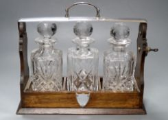 An oak three bottle tantalus, with key, decanters not matching, width 35cmCONDITION: Tantalus