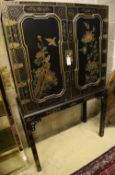 A Chinese black-lacquered and painted cabinet on stand, width 106cm, depth 46cm, height 173cm