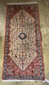 A Hamadan peach ground rug, 144 x 66cm