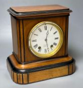 A walnut cased and ebonised mantel clock retailed by JW Benson, French movement striking on a