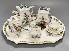 A late 19th century French porcelain flower encrusted cafe au lait set, on stand, stand