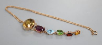 A yellow metal and graduated oval multi gem set pendant, on a yellow metal chain, including citrine,