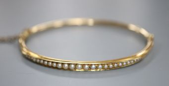A cased Edwardian yellow metal and graduated seed pearl set hinged bracelet, interior 56mm, gross