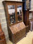A mid 18th century style walnut bureau bookcase, with two mirrored doors enclosing a single