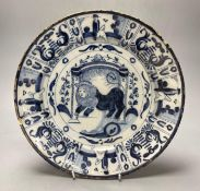 An 18th century Delft blue and white charger centred by a lion, with figural and foliate border,