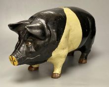 A large heavy cast iron saddle back pig money bank, circa 1950's, length 46cmCONDITION: Structurally