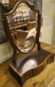 A shield-shaped swing frame mahogany toilet mirror, cross-banded and line-inlaid, the serpentine-