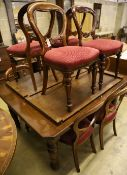 A late Victorian walnut extending dining table with two spare leaves and ten Victorian style