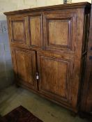 A 19th century French panelled walnut press cupboard fitted upper and lower pairs of doors, width