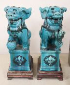 A pair of Chinese turquoised glazed lion dogs, on wood stands, height 58cm overall