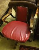 A 1920's oak swivel desk chair, the back and seat cushion covered in red hide, width 63cm, depth