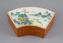 A Chinese coral ground fan-shaped box and cover, bearing a Qianlong mark, the top painted in famille