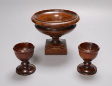 A 19th century turned amboyna urn, 11cm and two late Georgian turned mahogany egg cups, 6.5cm